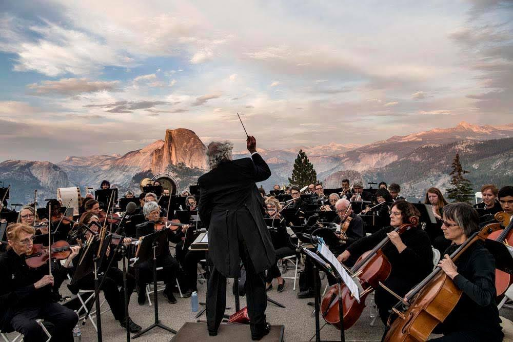 The Mariposa Symphony Orchestra performing at Glacier Point in Yosemite National Park for their Our Nation's Nature Tour Finale. Photograph by Al Golub - courtesy of the National Park Service.