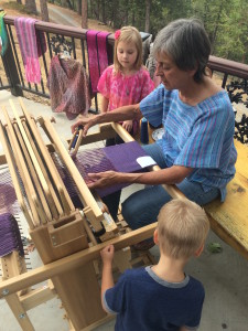 District 2 Artist Jan DeShera demos her weaving skills for youngsters